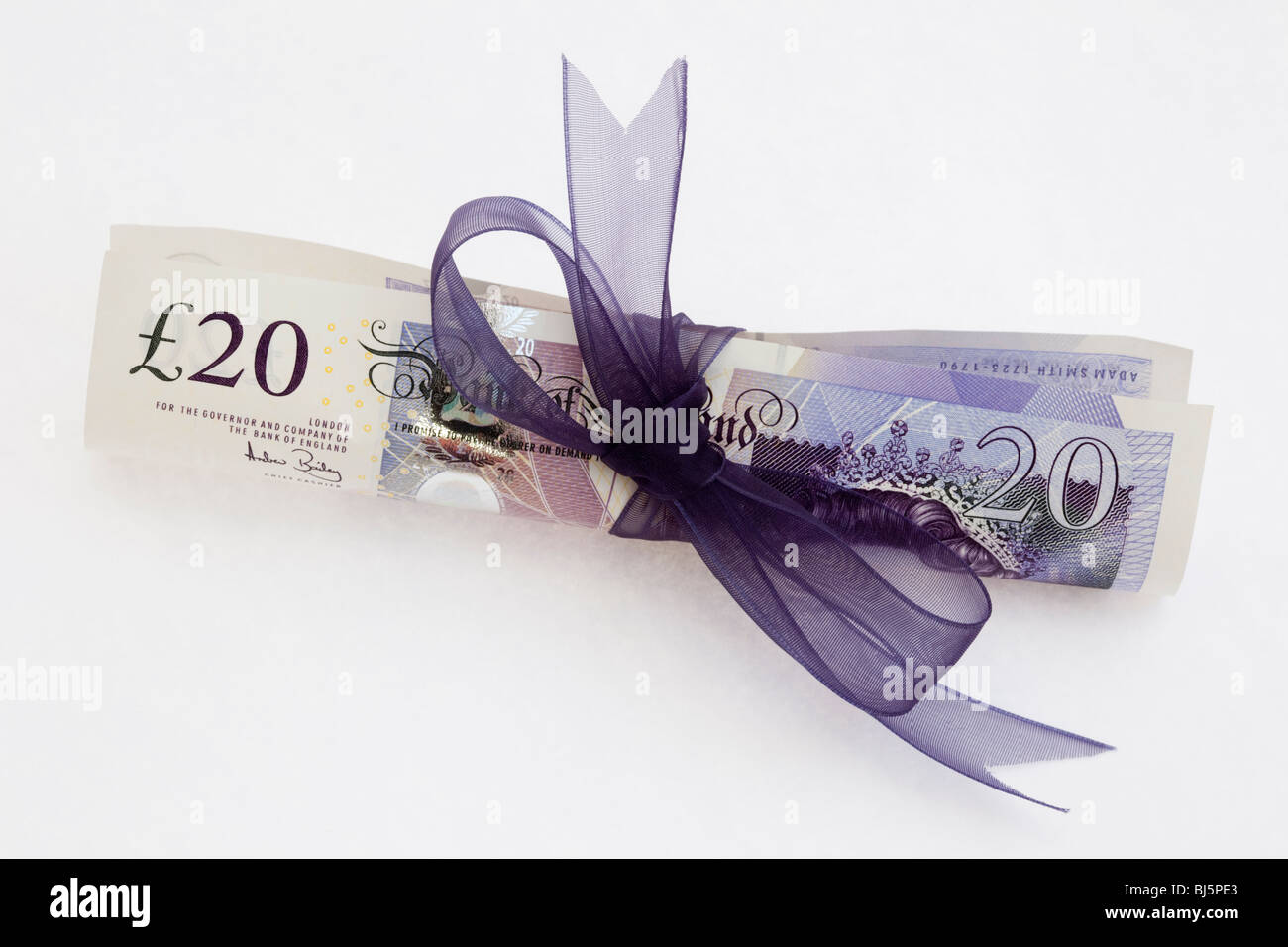 Rolled up sterling £20 pound note GBP tied up with a purple ribbon on a plain white background. Giving give - Stock Image