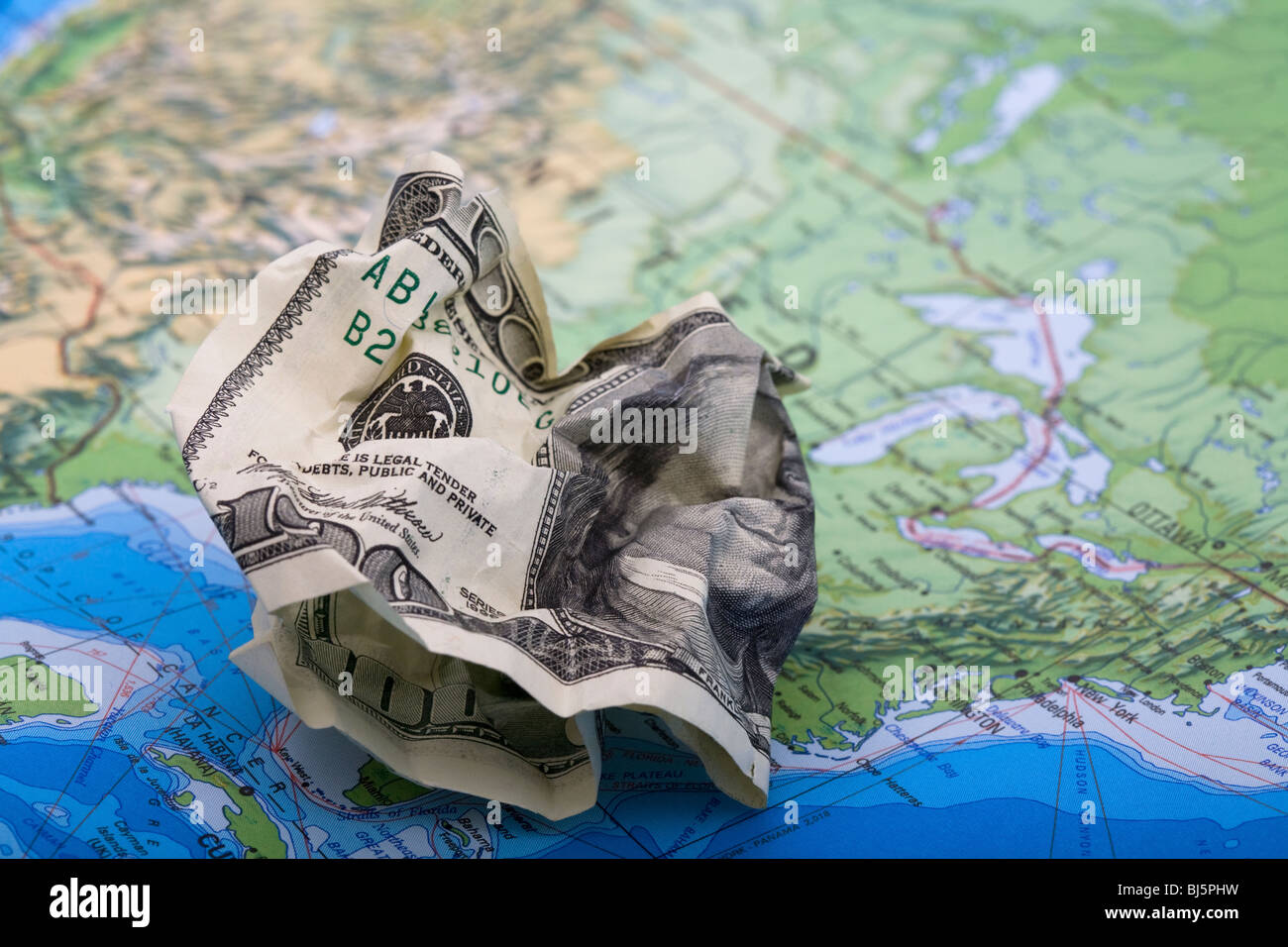 Throwing money away. A hundred dollar bill on a world map - Stock Image