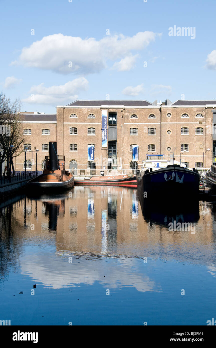 The Museum of Docklands building reflected in the water of West India Dock - Stock Image