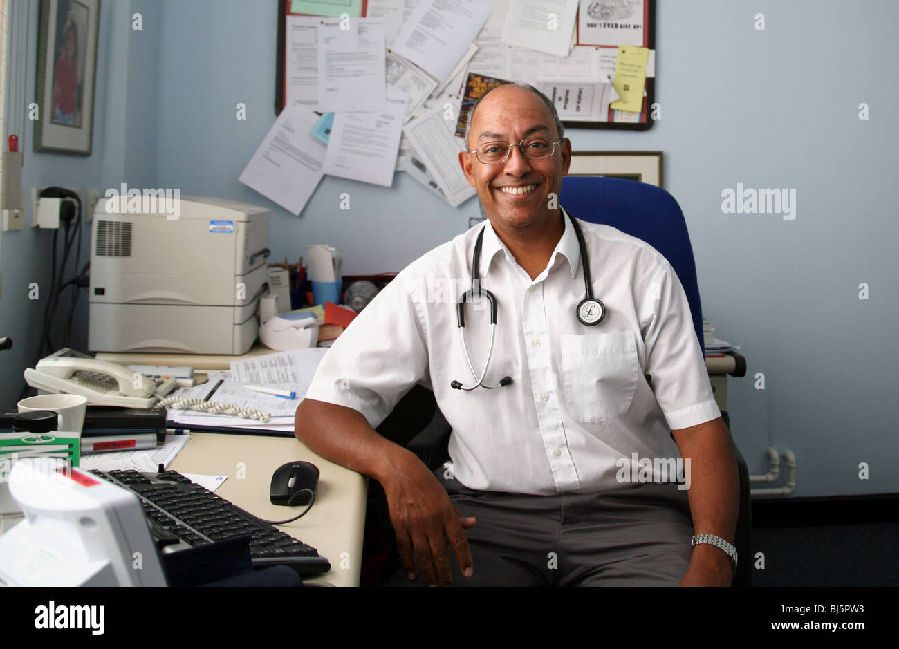 A model-released male NHS GP doctor of asian origin in his surgery, UK - Stock Image