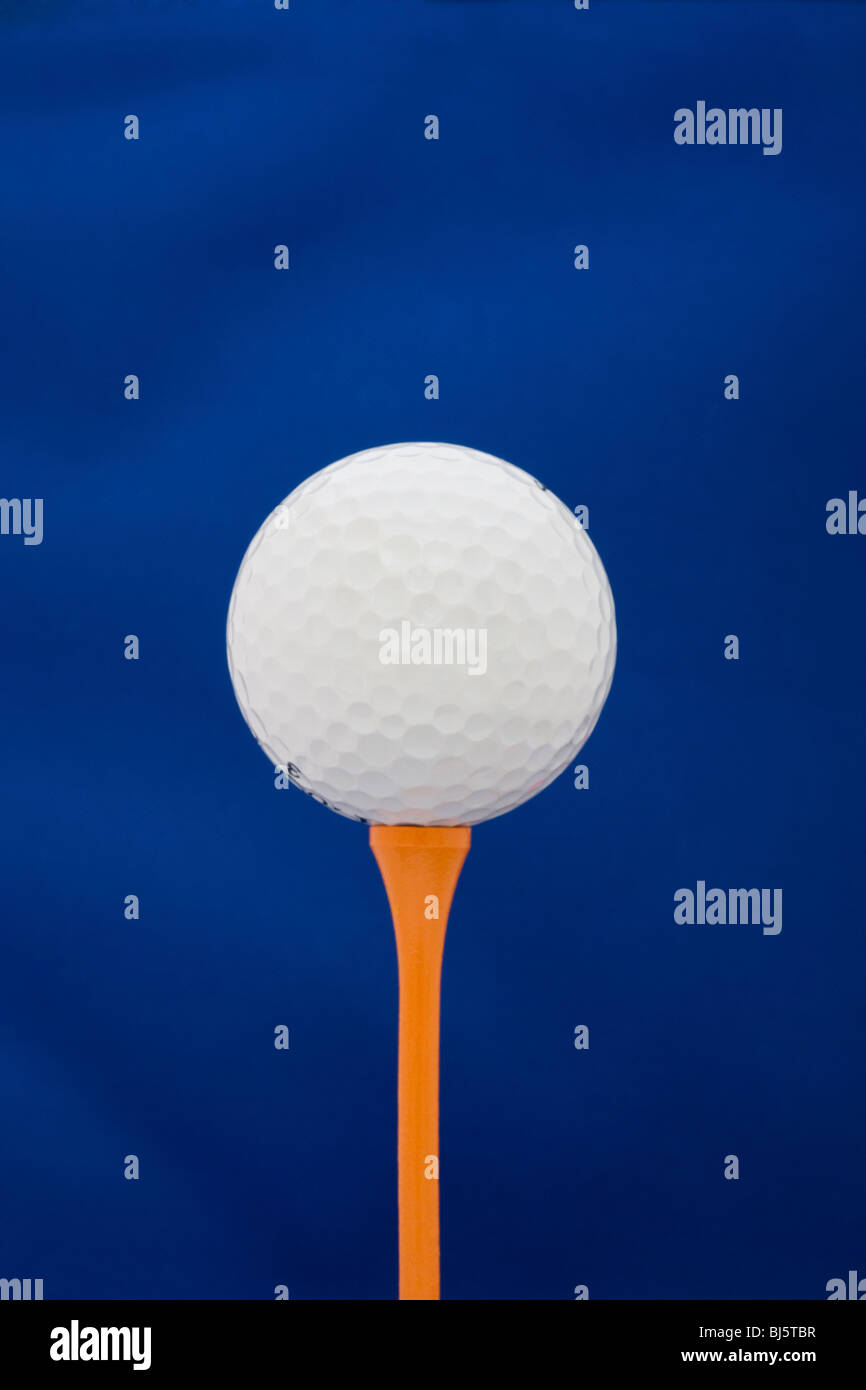 Golfball on an orange tee against a blue studio background - Stock Image