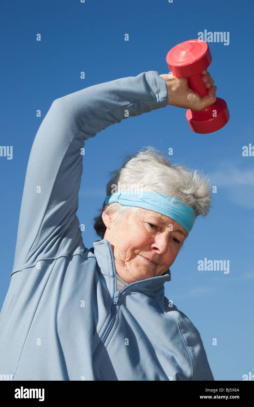 Active senior woman wearing a sweatband bending sideways whilst exercising using dumbbell hand weights working out - Stock Image