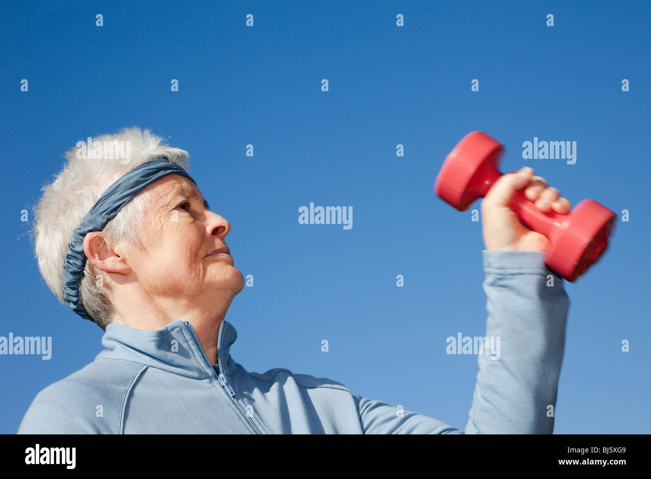 Active senior woman pensioner doing a workout wearing a sweatband whilst exercising with dumbbell hand weights to - Stock Image