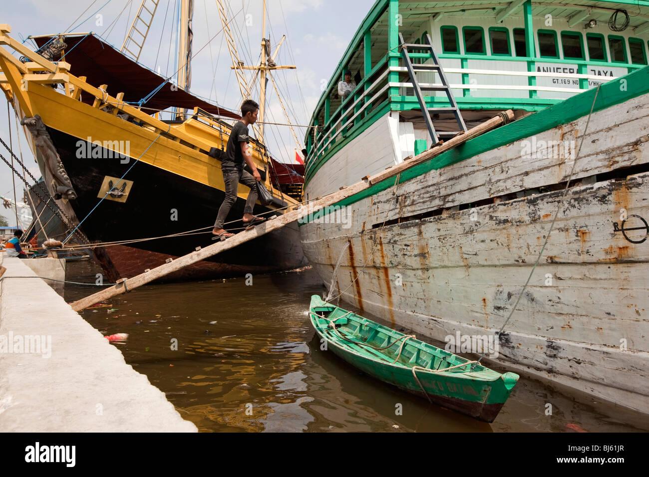 Indonesia, Java, Jakarta, Sunda Kelapa, worker walking up wooden sailing cargo boat gangplank - Stock Image