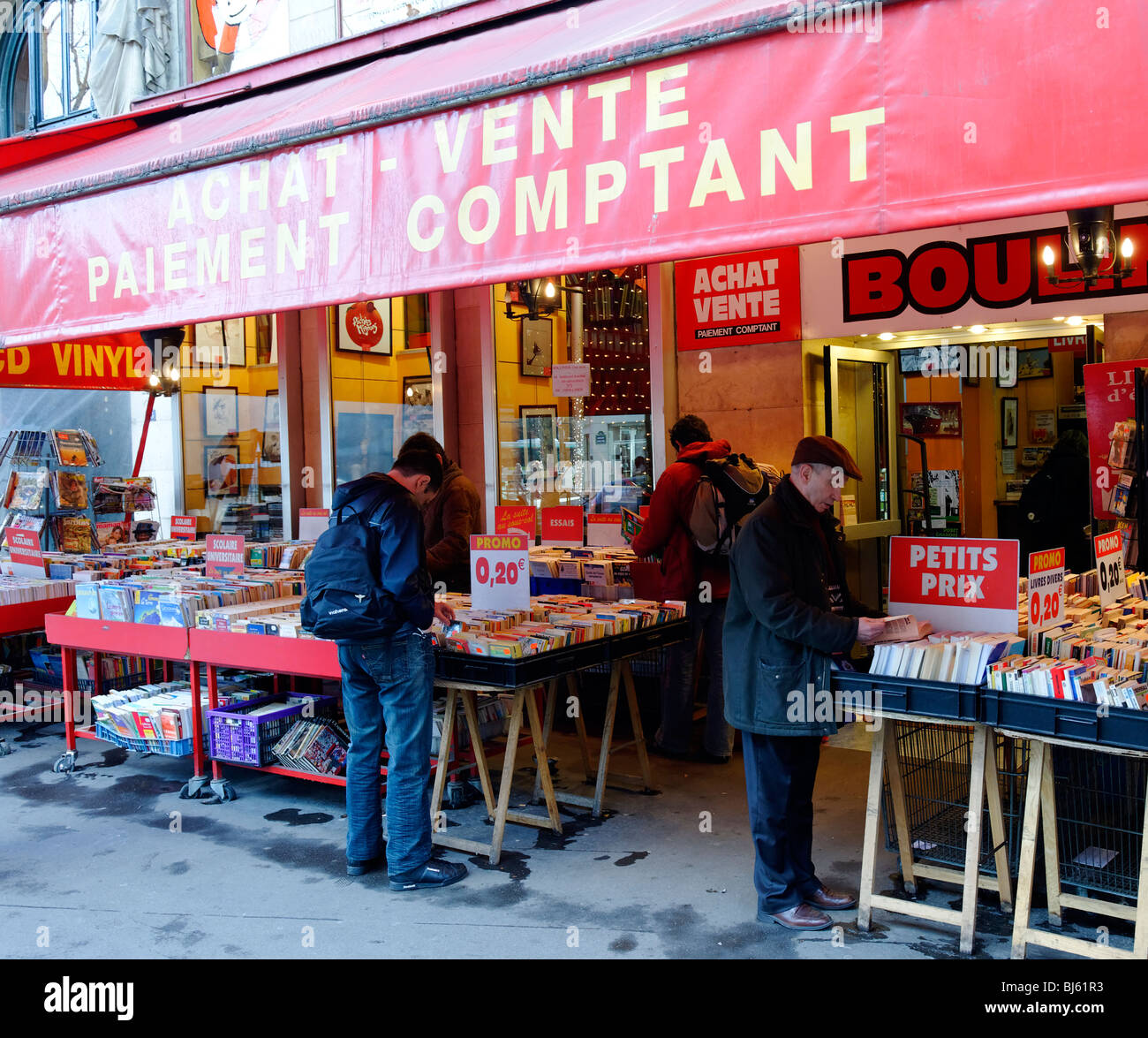Parisians browsing book stores along Place Saint-Michel in the Latin Quarter of Paris. - Stock Image