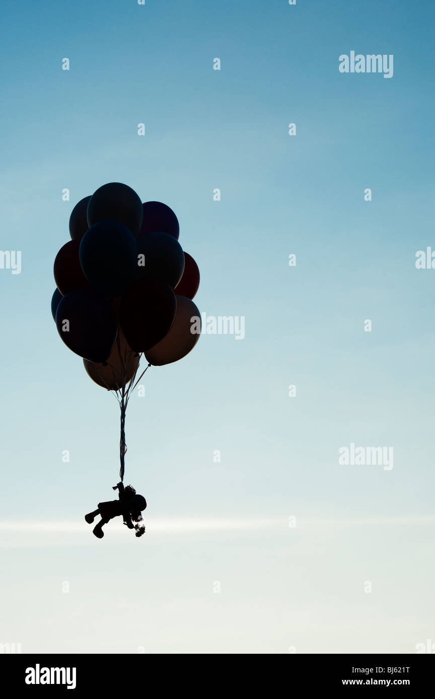 Rag doll holding onto helium balloons floating away. Silhouette - Stock Image