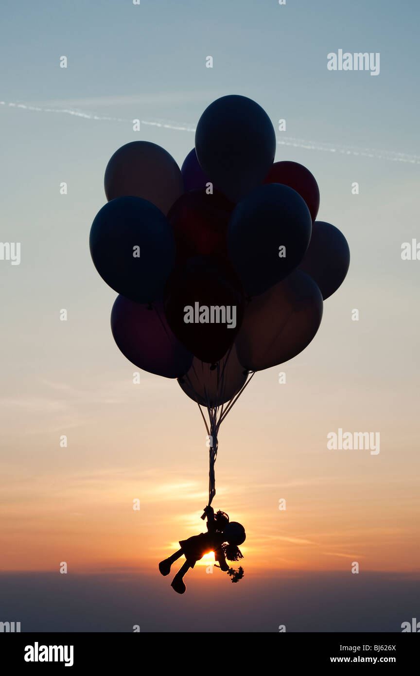Rag doll holding onto helium balloons floating away at sunset. Silhouette - Stock Image
