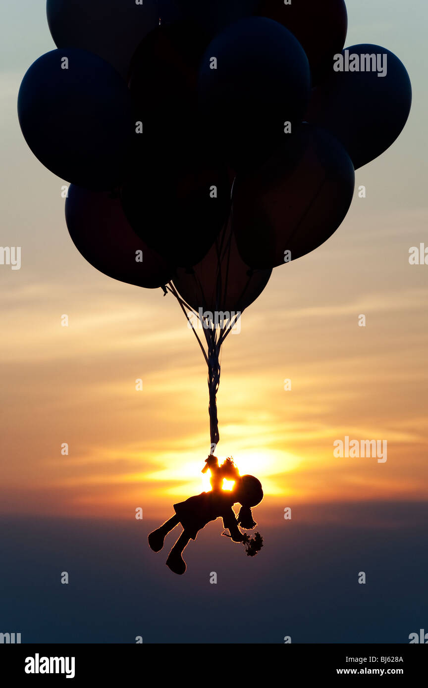rag doll holding onto helium balloons floating away at sunset stock