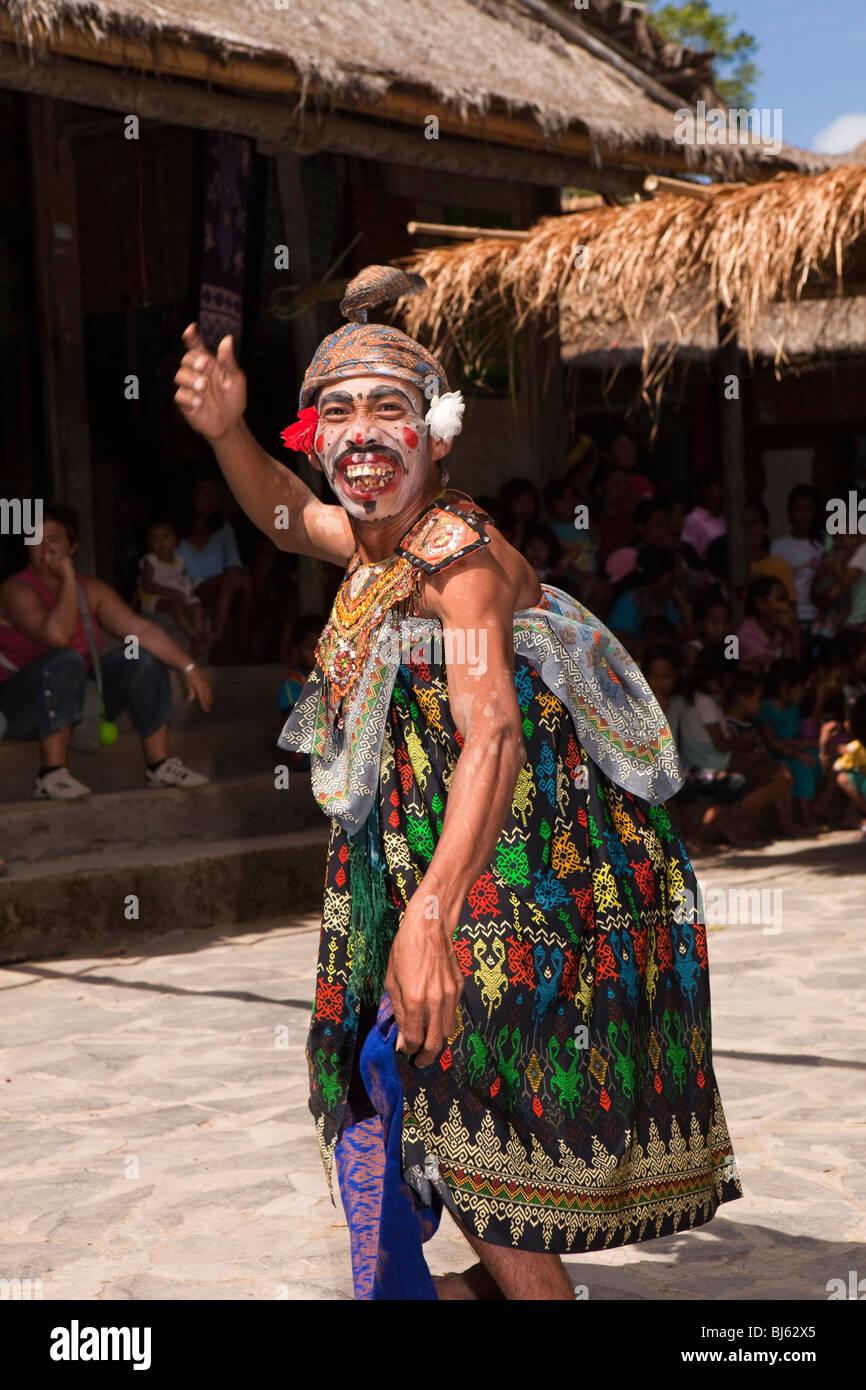 Indonesia, Lombok, Sade, traditional Sasak village, colourfully dressed jester making amusing facial expression - Stock Image