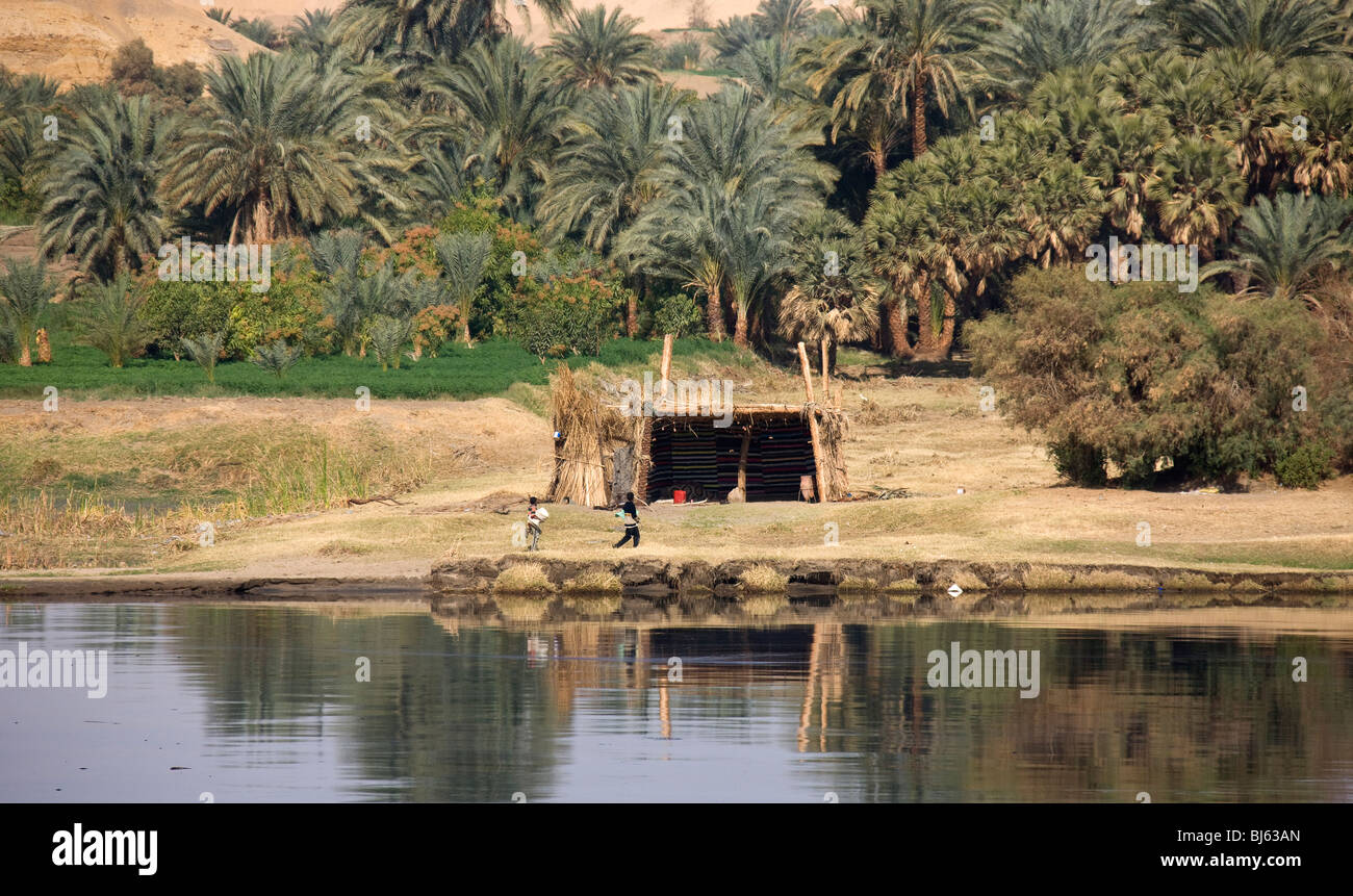 Two children outside basic habitation on the bank of the River Nile. - Stock Image