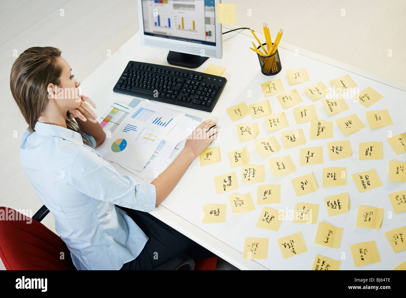 tired business woman with adhesive notes on table. High angle view Stock Photo