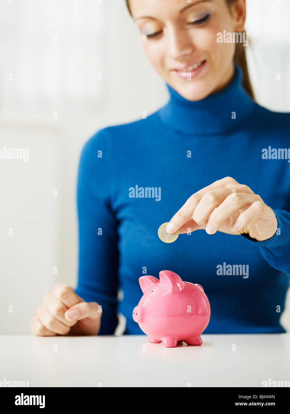 woman putting 1 euro in small piggy bank. Selective focus, Copy space - Stock Image