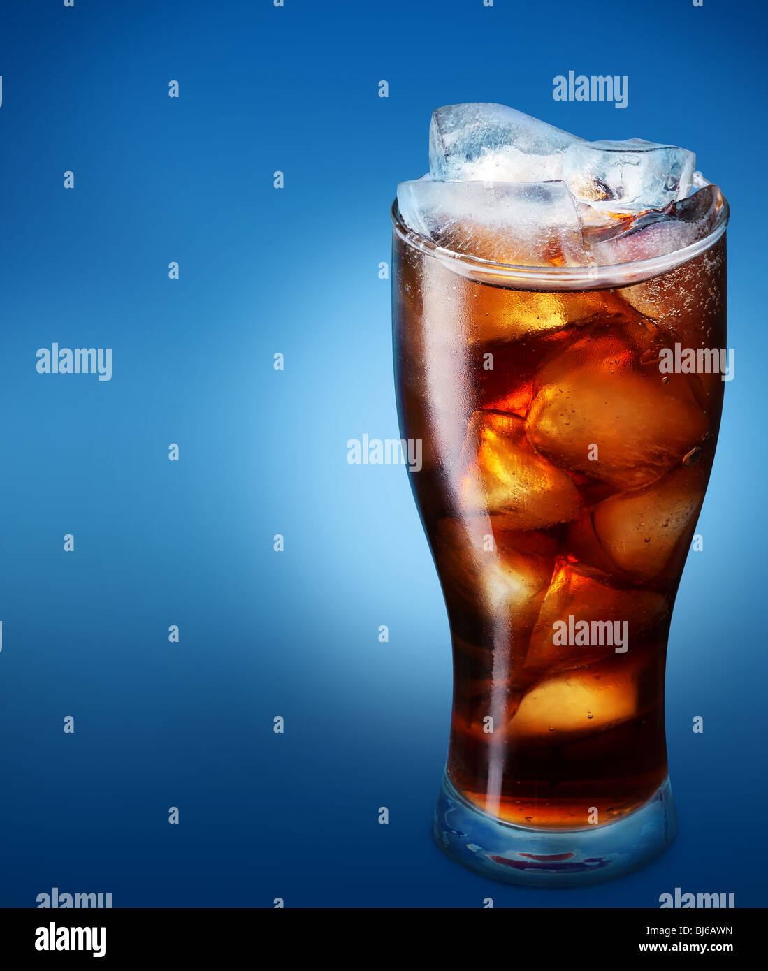Glass of cola with ice on a blue background - Stock Image