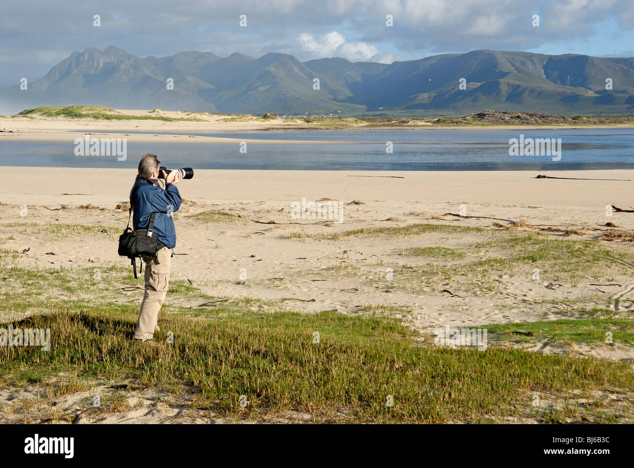 Man taking photograph of a landscape with telephoto in the morning, Flamingo lake estuary near Hermanus, South Africa - Stock Image