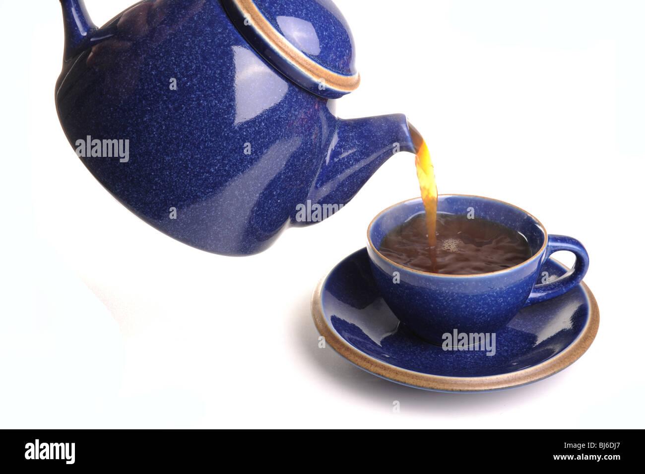 Tea pot pouring tea into a teacup, studio isolated - Stock Image