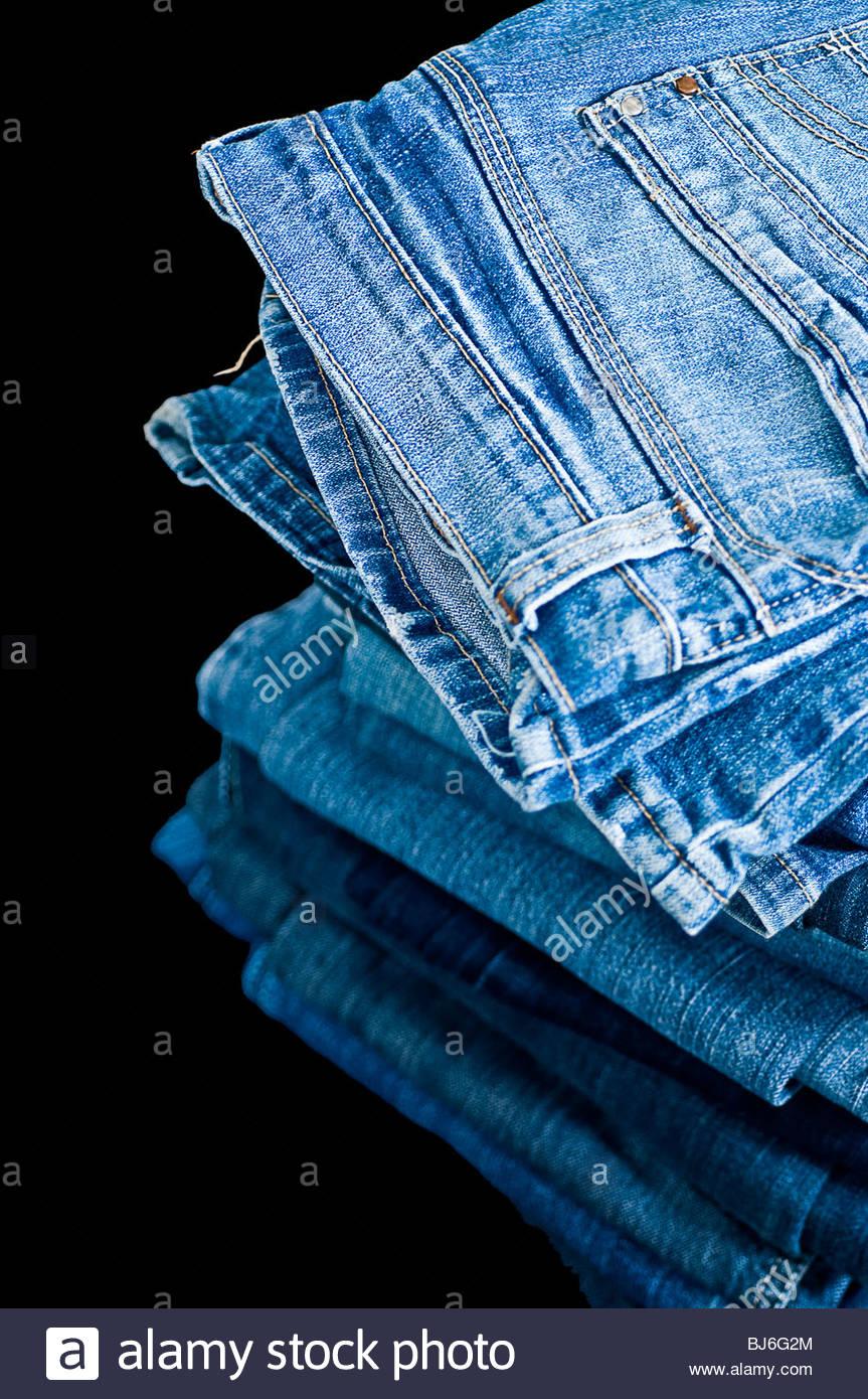 Pile of blue denim jeans - Stock Image