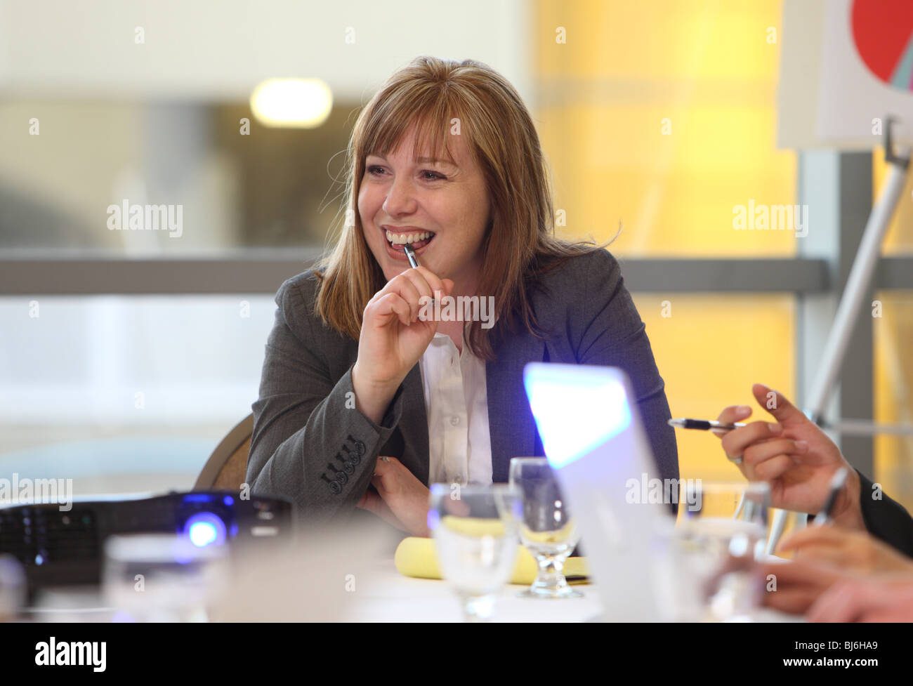 Business woman smiles in board room meeting - Stock Image