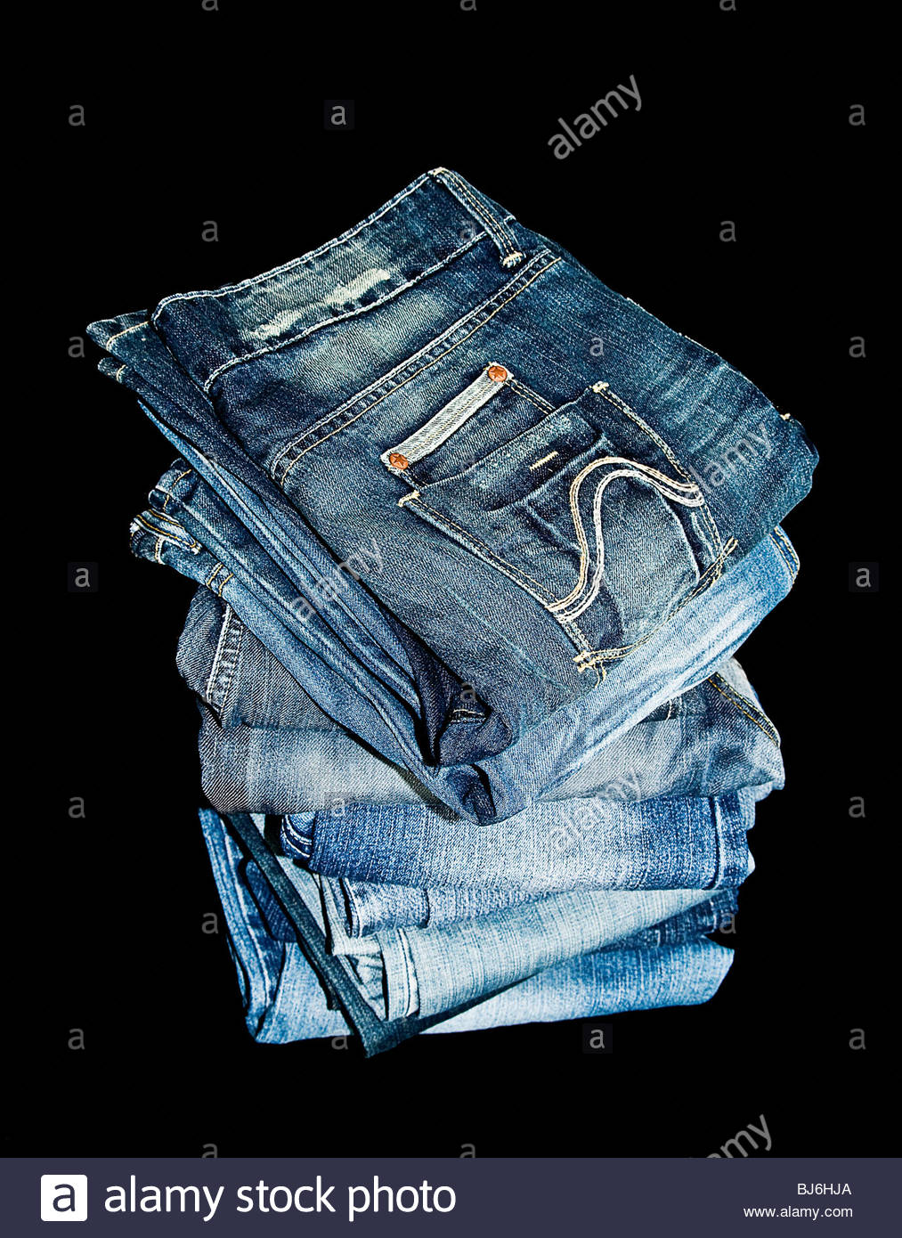 Pile of blue denim jeans - Stock Image