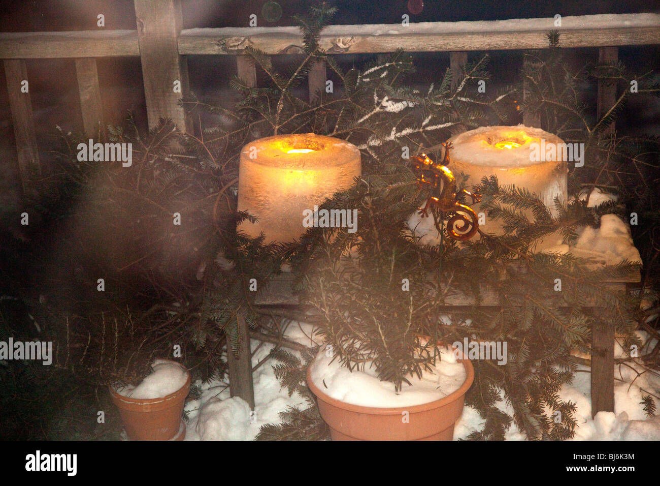 Candles burning on deck in winter artistically surrounded by evergreen bows and snow. St Paul Minnesota USA - Stock Image