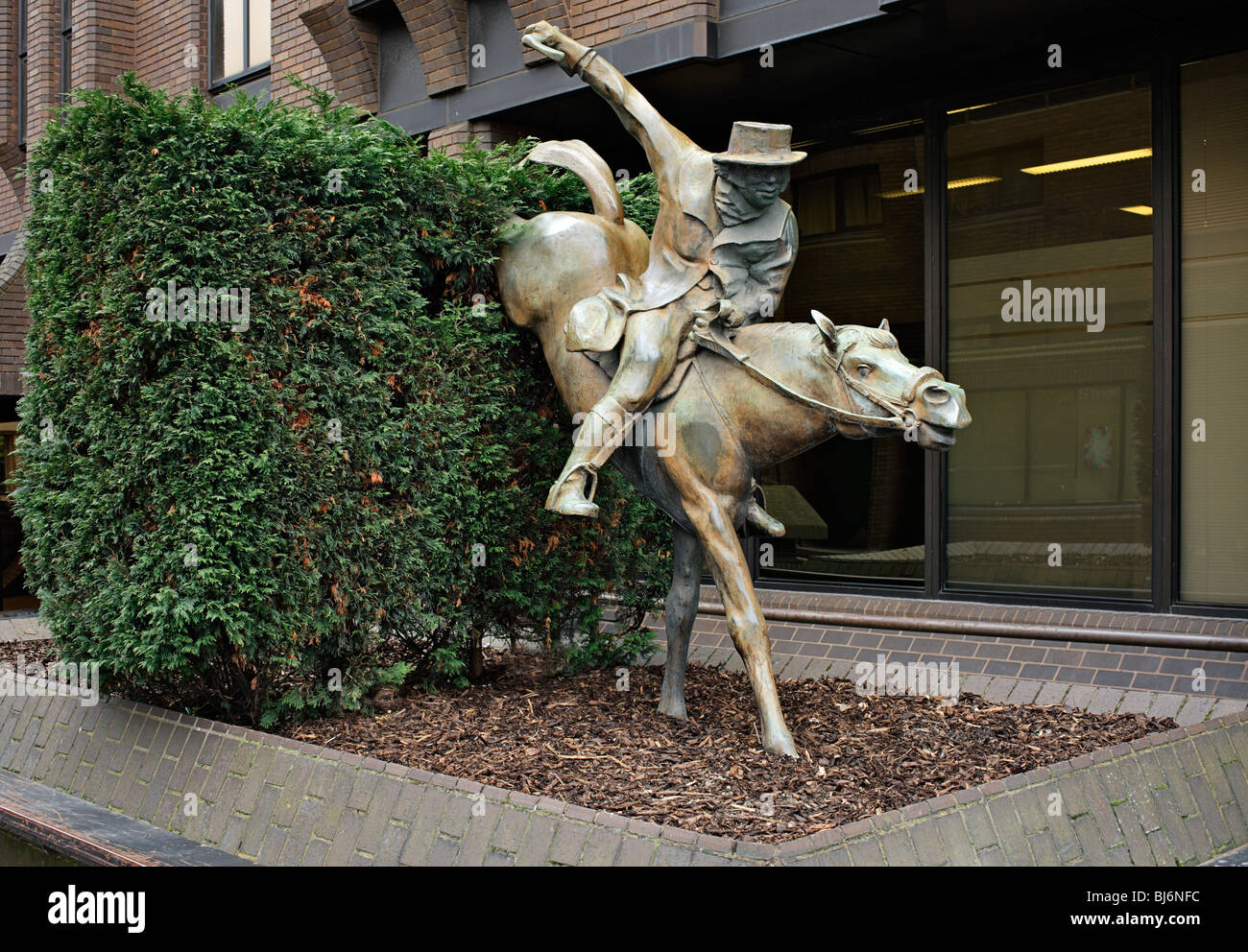 Statue of a Jockey riding a horse over a hedge. - Stock Image
