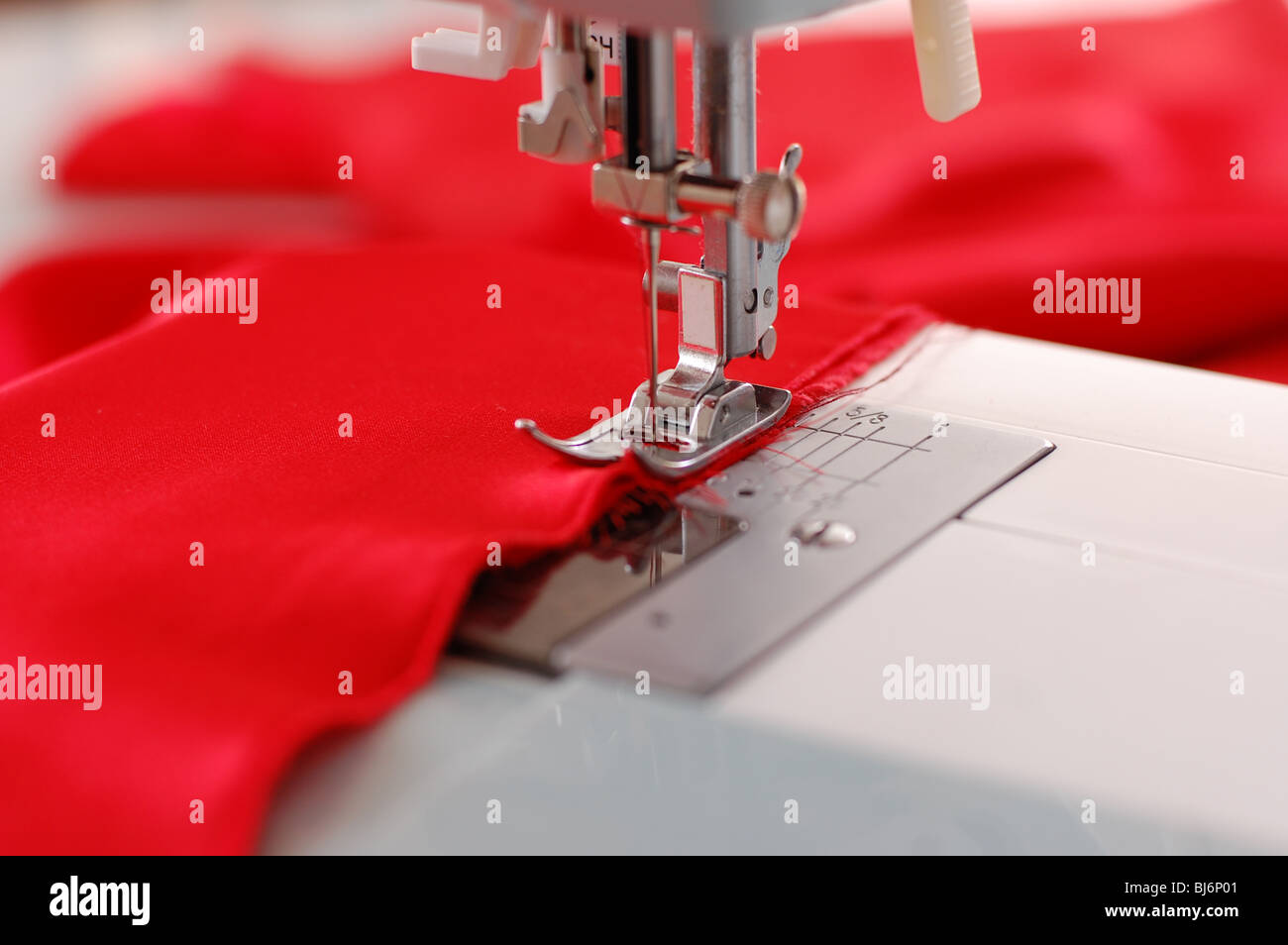 Sewing machine detail with the red thread and cloth - Stock Image