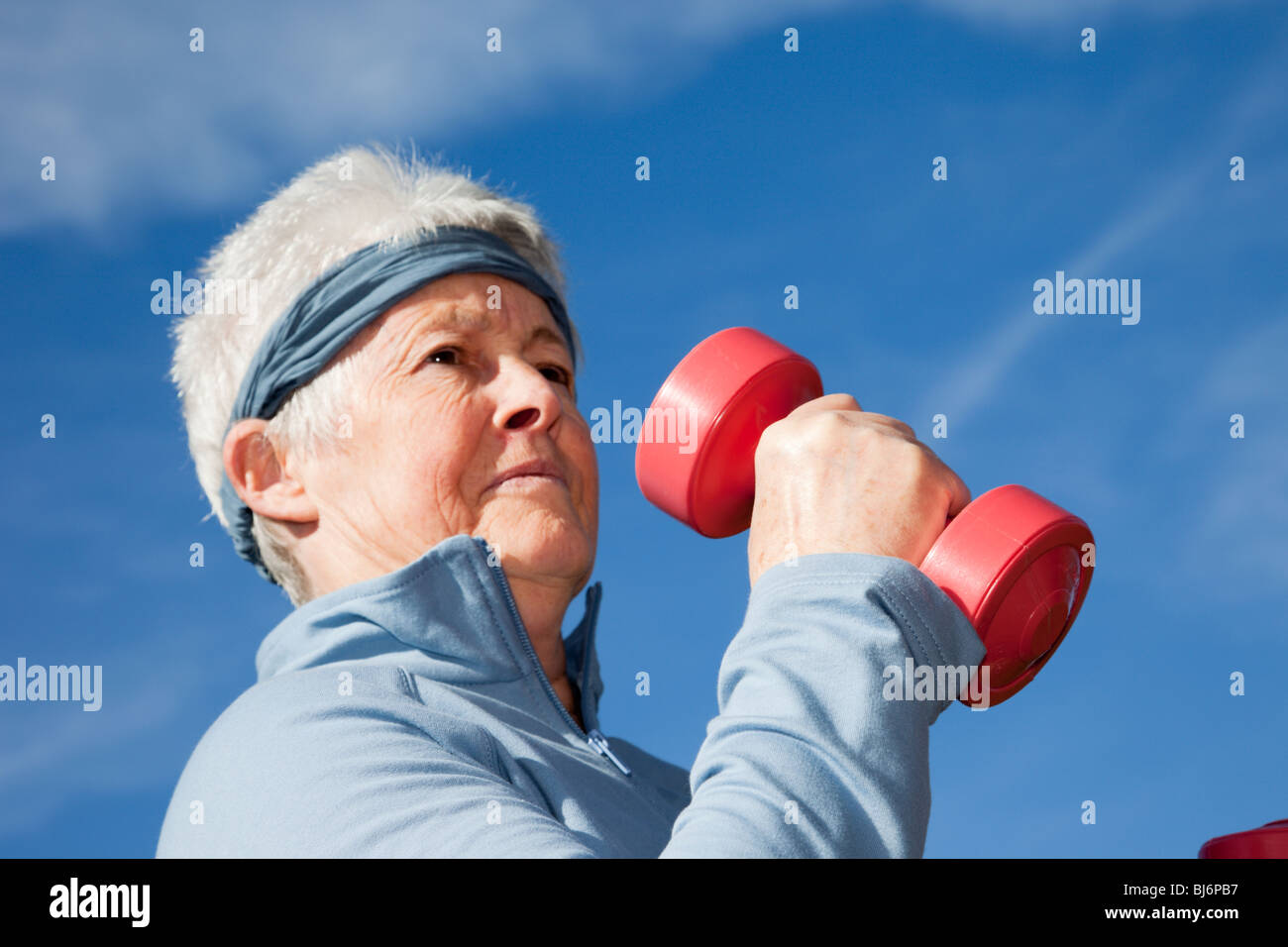 Senior woman wearing a sweatband whilst exercising with dumbbell hand weights outdoors. Britain, UK. - Stock Image