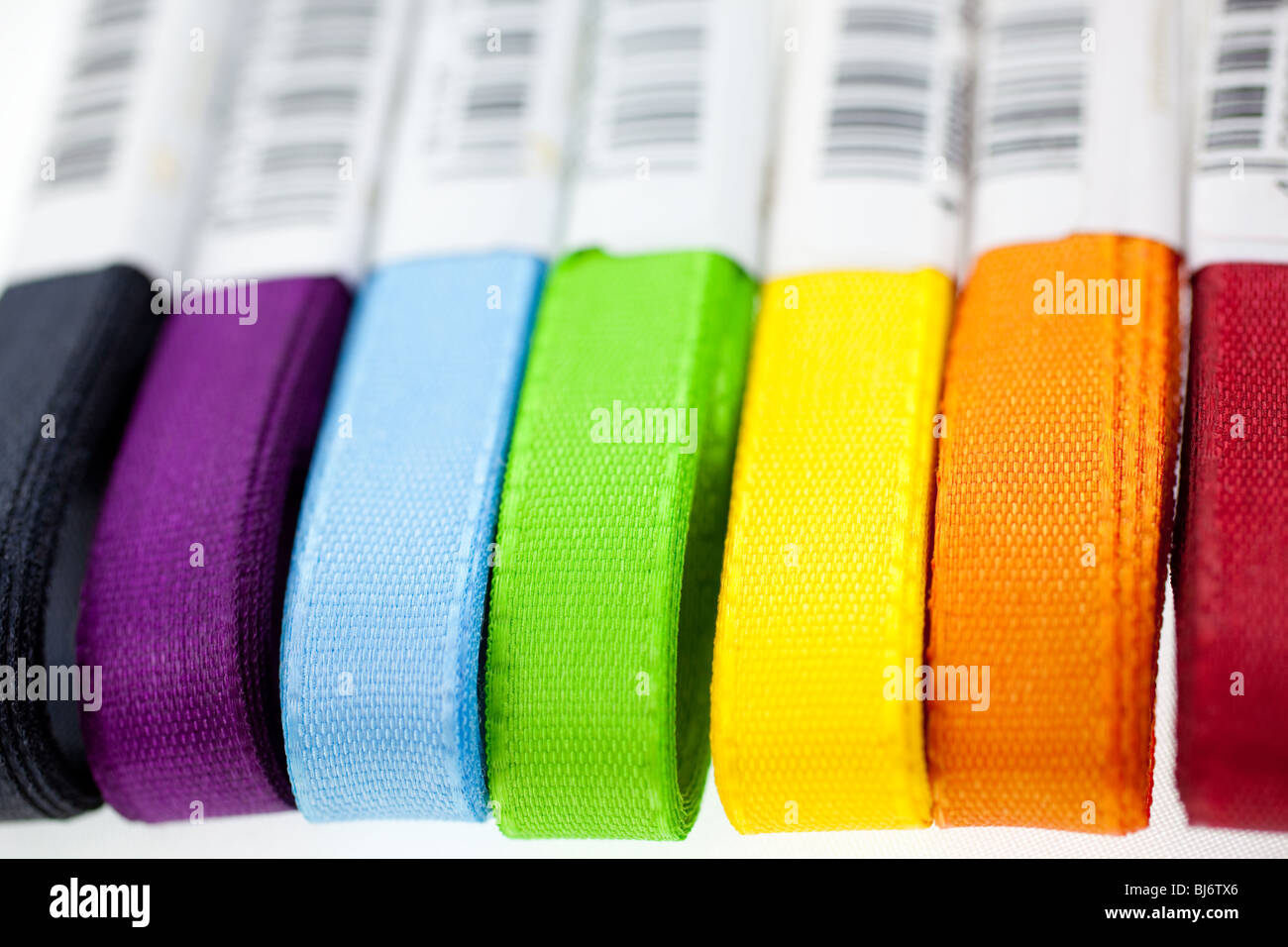 seven rainbow colored ribbons on white background. closeup - Stock Image