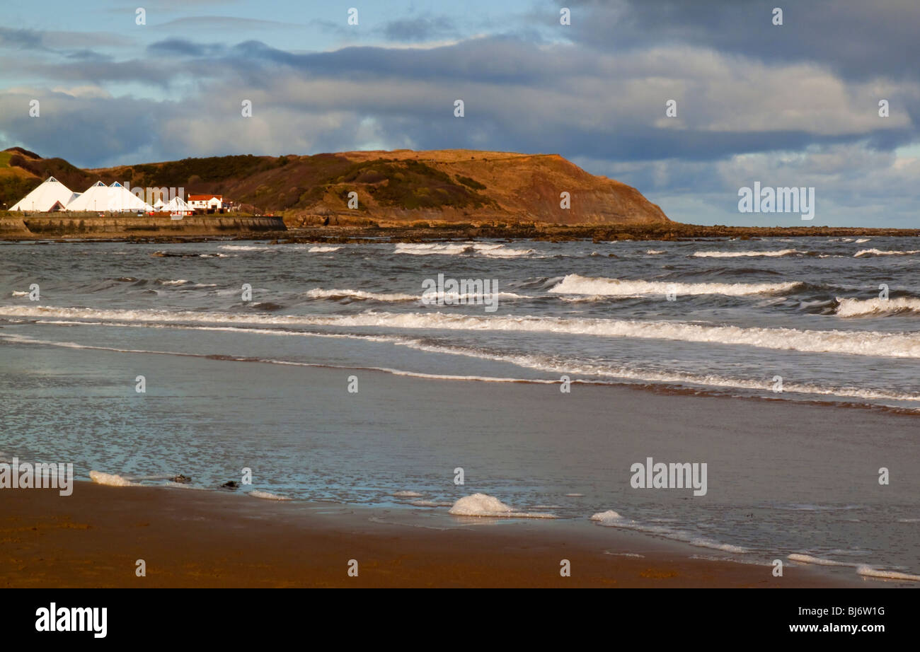 The beach at Scarborough North Bay in North Yorkshire England UK looking north with waves in the foreground - Stock Image