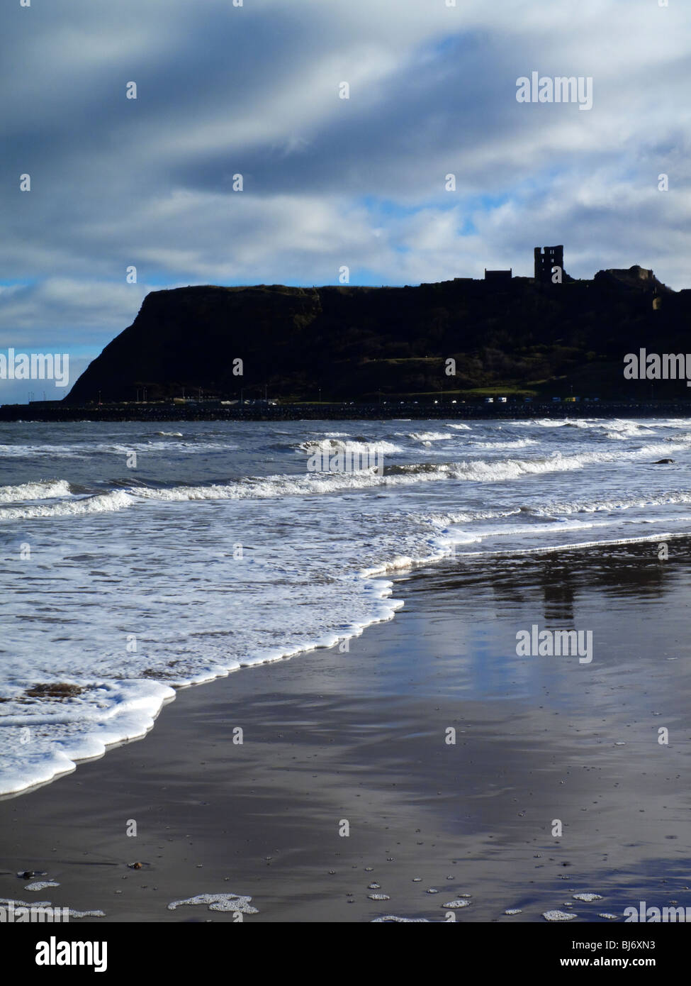 The beach at Scarborough North Bay in North Yorkshire England UK with the castle visible on the clifftop and waves - Stock Image