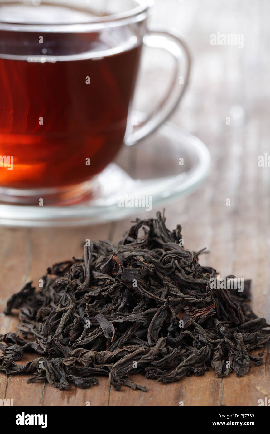 Heap of dried tea leaves and a cup of black tea - Stock Image