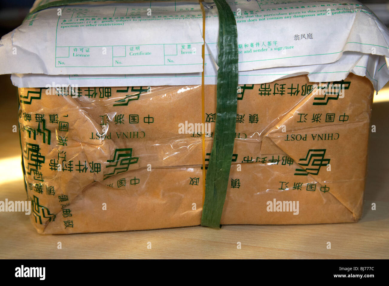 parcel sent from china received in the UK with chinese packaging and customs clearance form - Stock Image