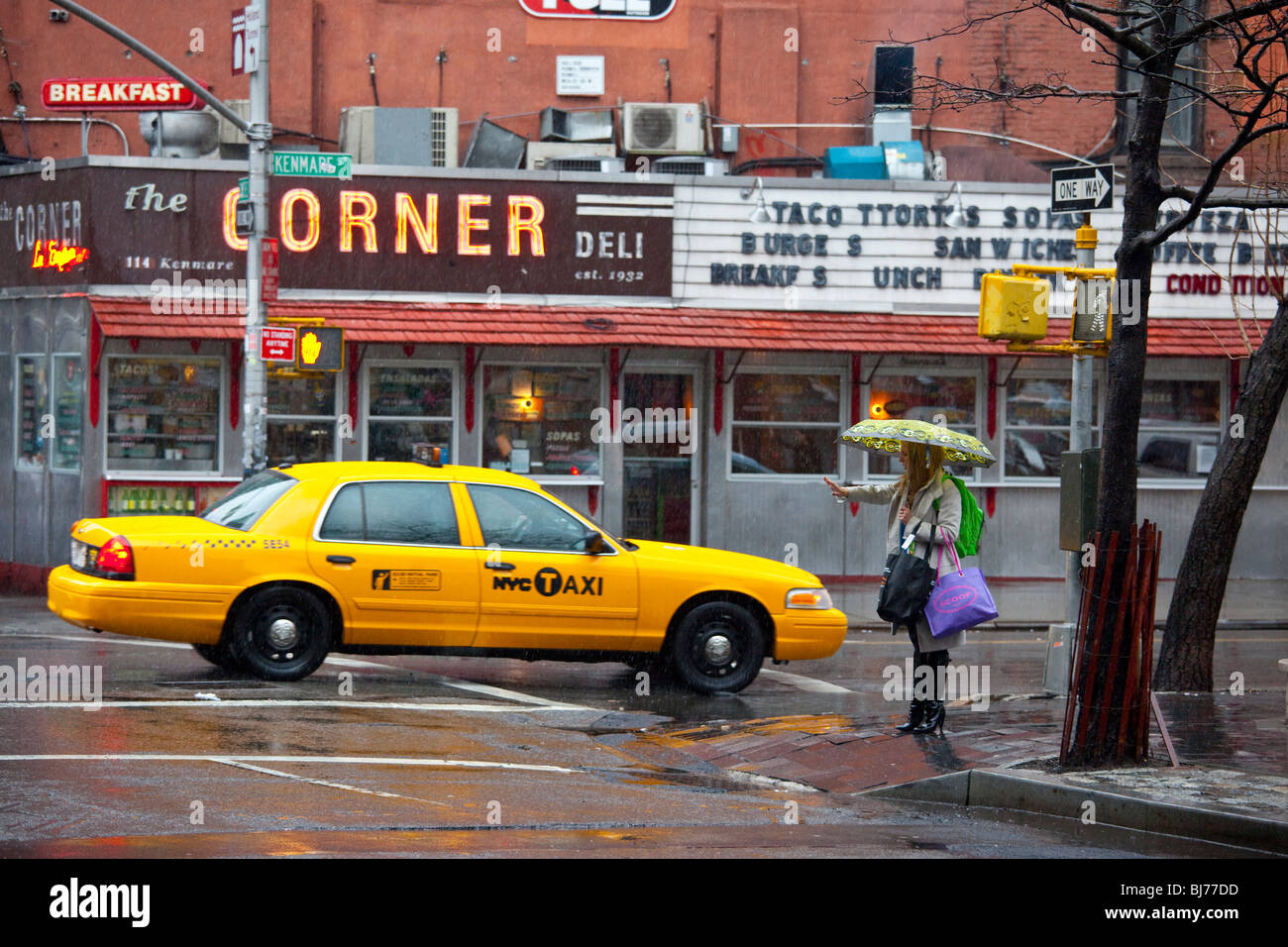 Woman hailing a taxicab in Soho, New York City - Stock Image