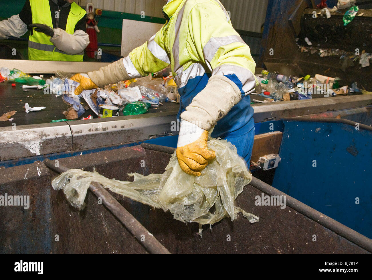 Recyclable waste sorting center. Employees on each side of the conveyor belt manually sort the different types of - Stock Image
