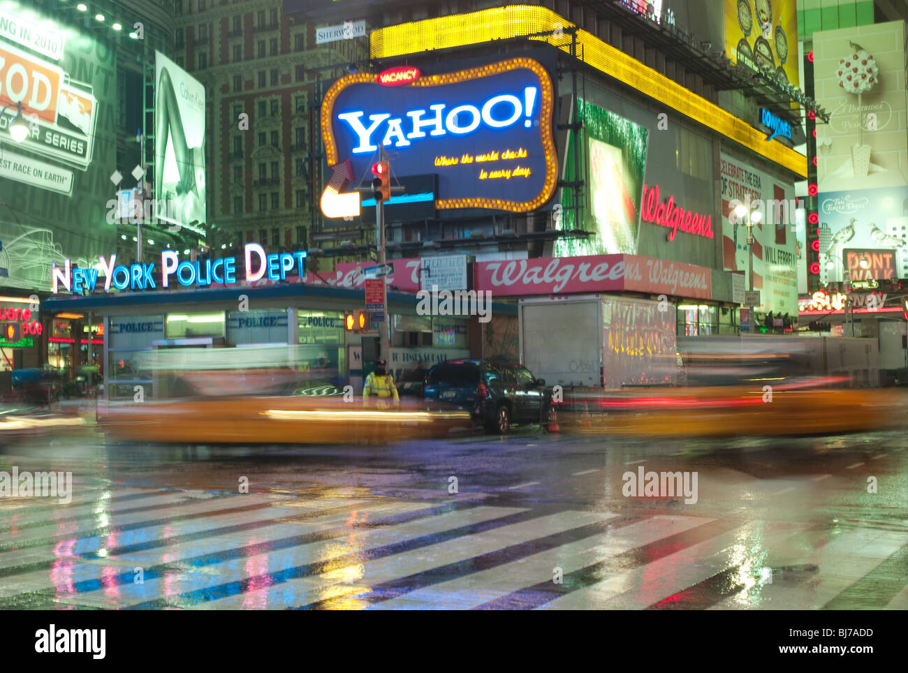Taxis in motion rushing past the NYPD station in Times Square on a rainy evening in New York City. - Stock Image