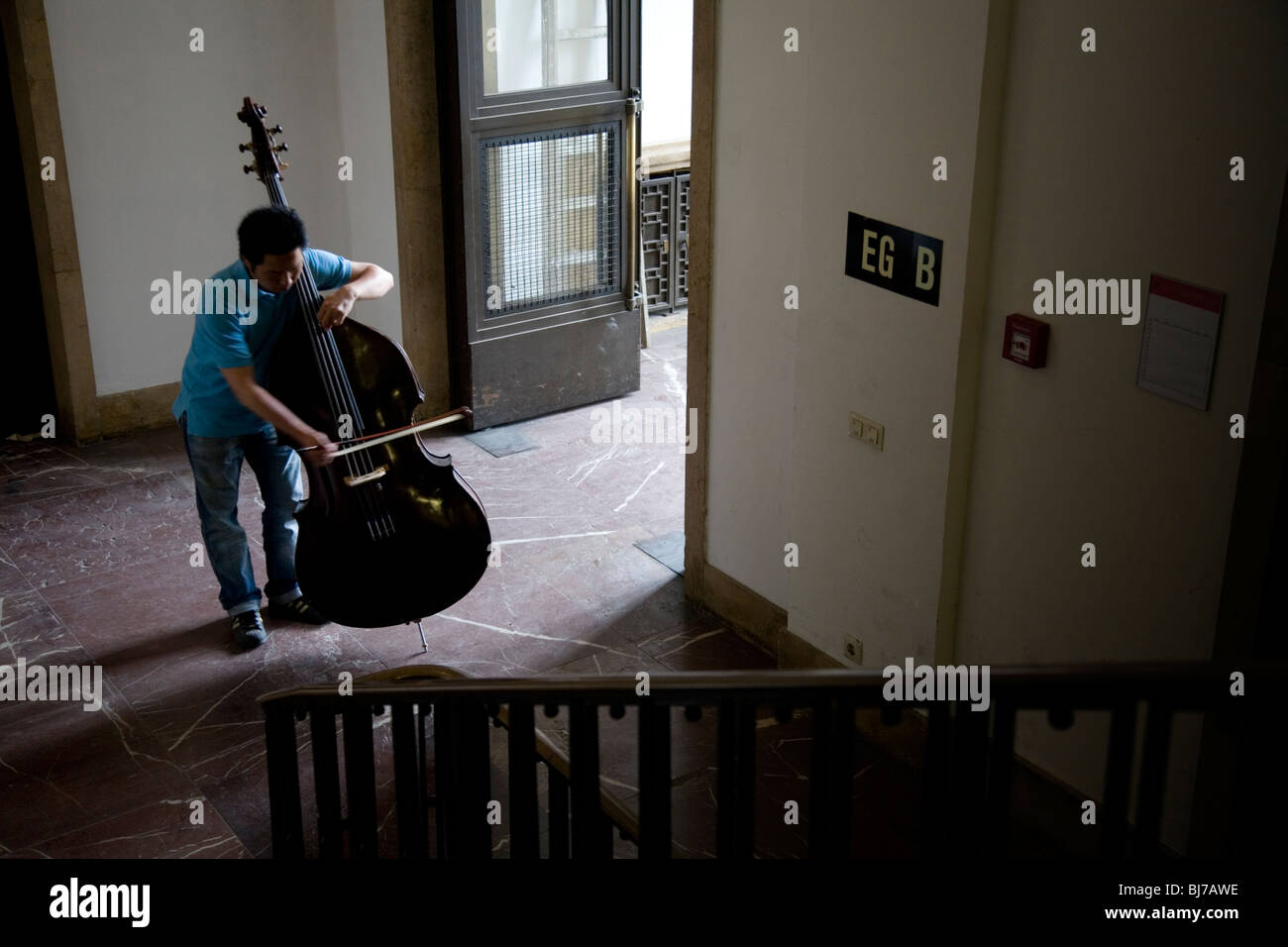 A Cello player rehearsing at the end of a staircase Stock Photo