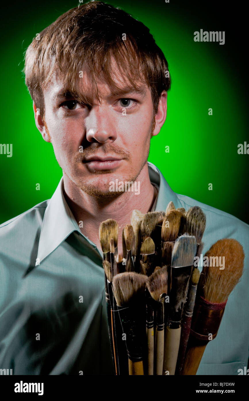 Portrait of an Artist on Green with Paint Brushes - Stock Image