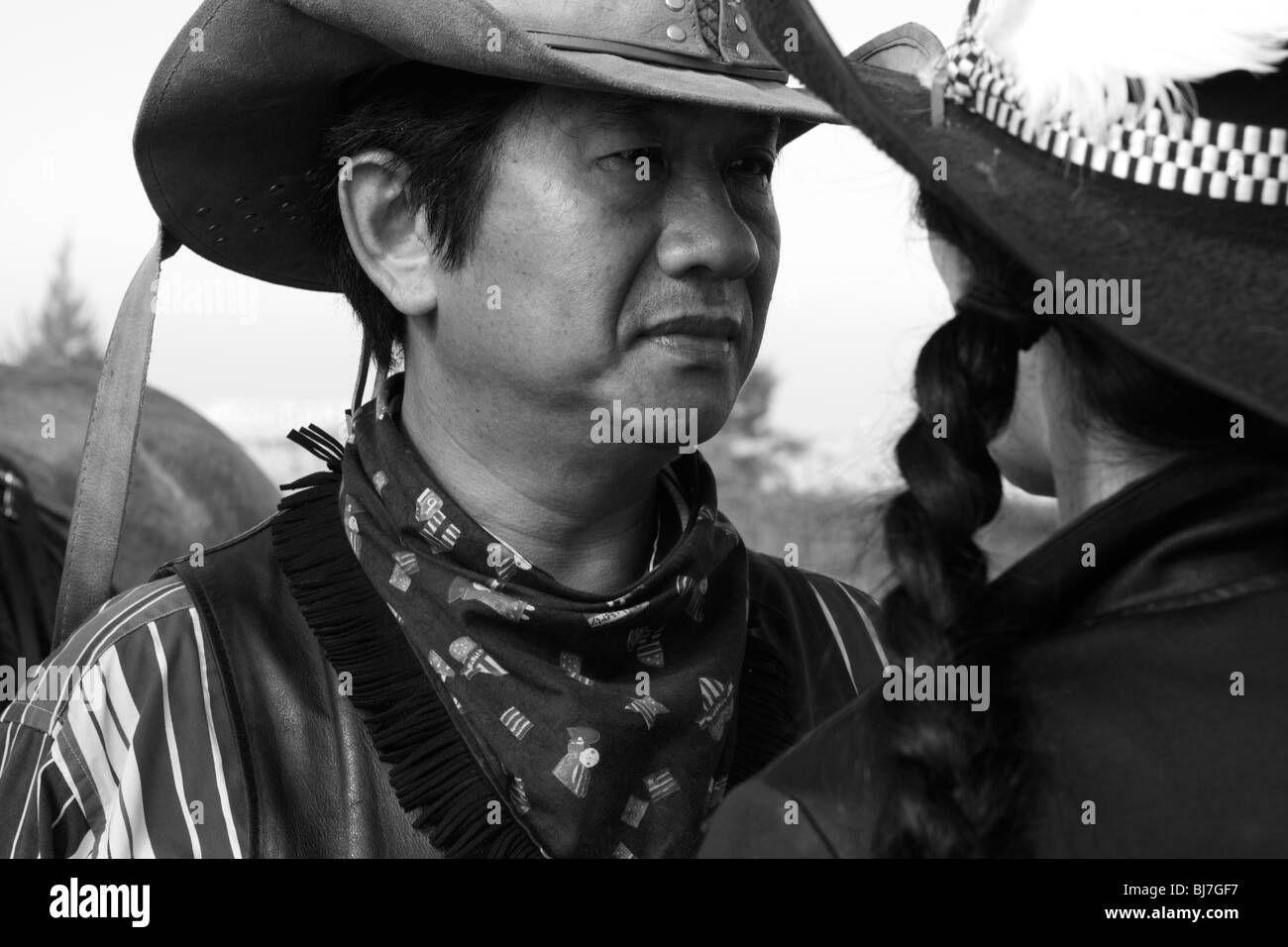 Asian horseback riders stand face to face. - Stock Image