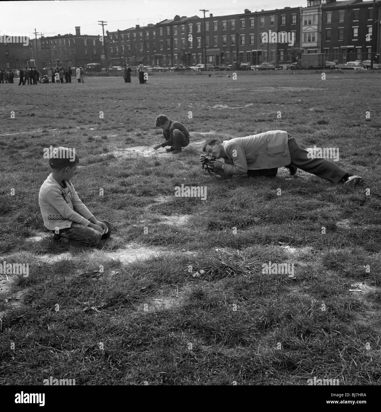A photographer photographs a small child using a 35mm rangefinder camera in a park in South Philadelphia. - Stock Image