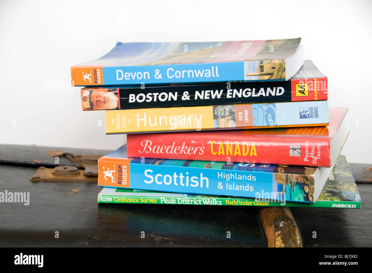 A selection of travel guide books on an old suitcase - Stock Image