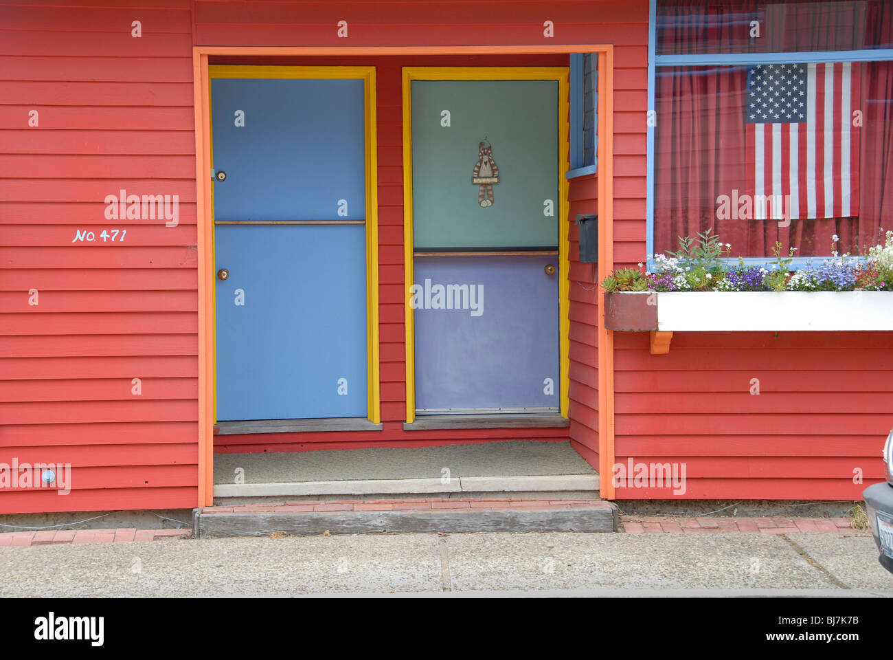 A multi colored cottage apartment with an American flag in the window. Stock Photo