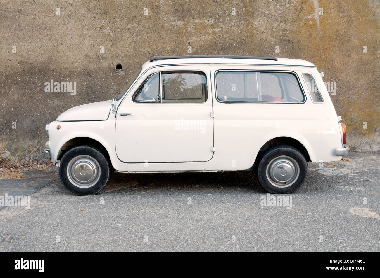 An old Fiat car parked on a side street in the village of Malfa, on the Aeolian Island of Salina, Italy. - Stock Image