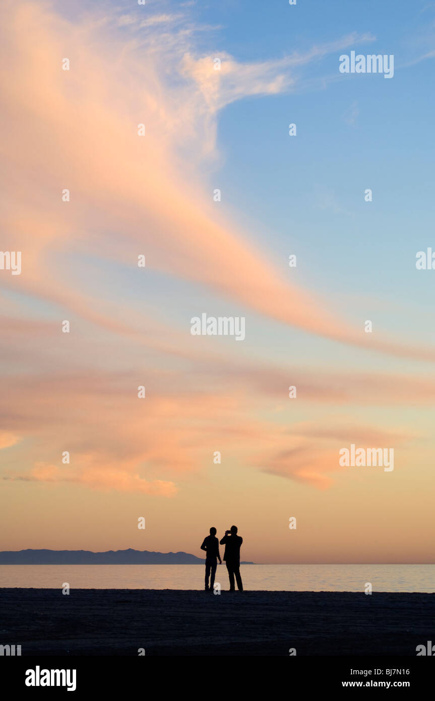 People photographing on the beach at sunset - Stock Image