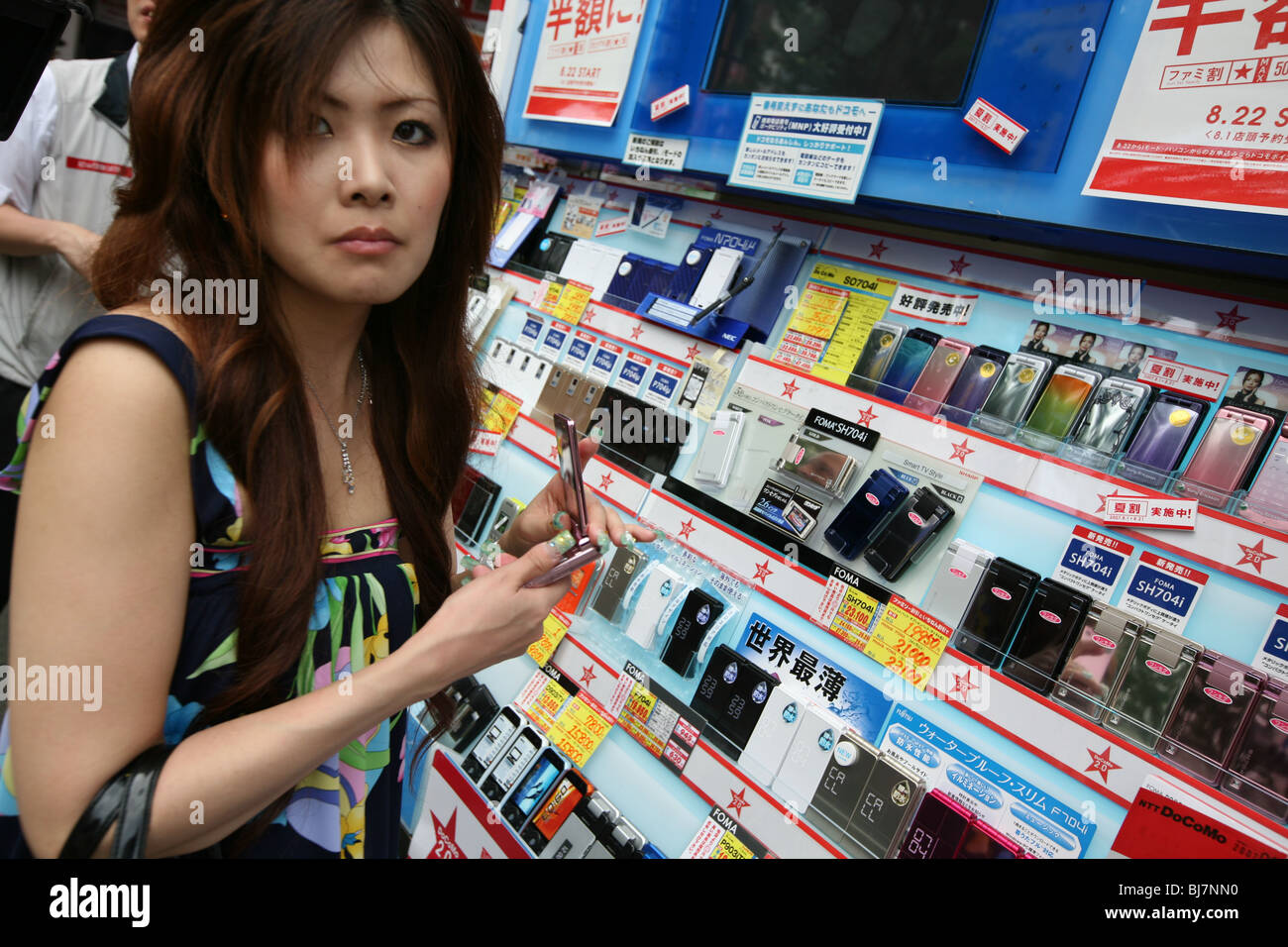 Customers shopping for new mobile telephones in phone store in Tokyo, Japan, 2007. - Stock Image
