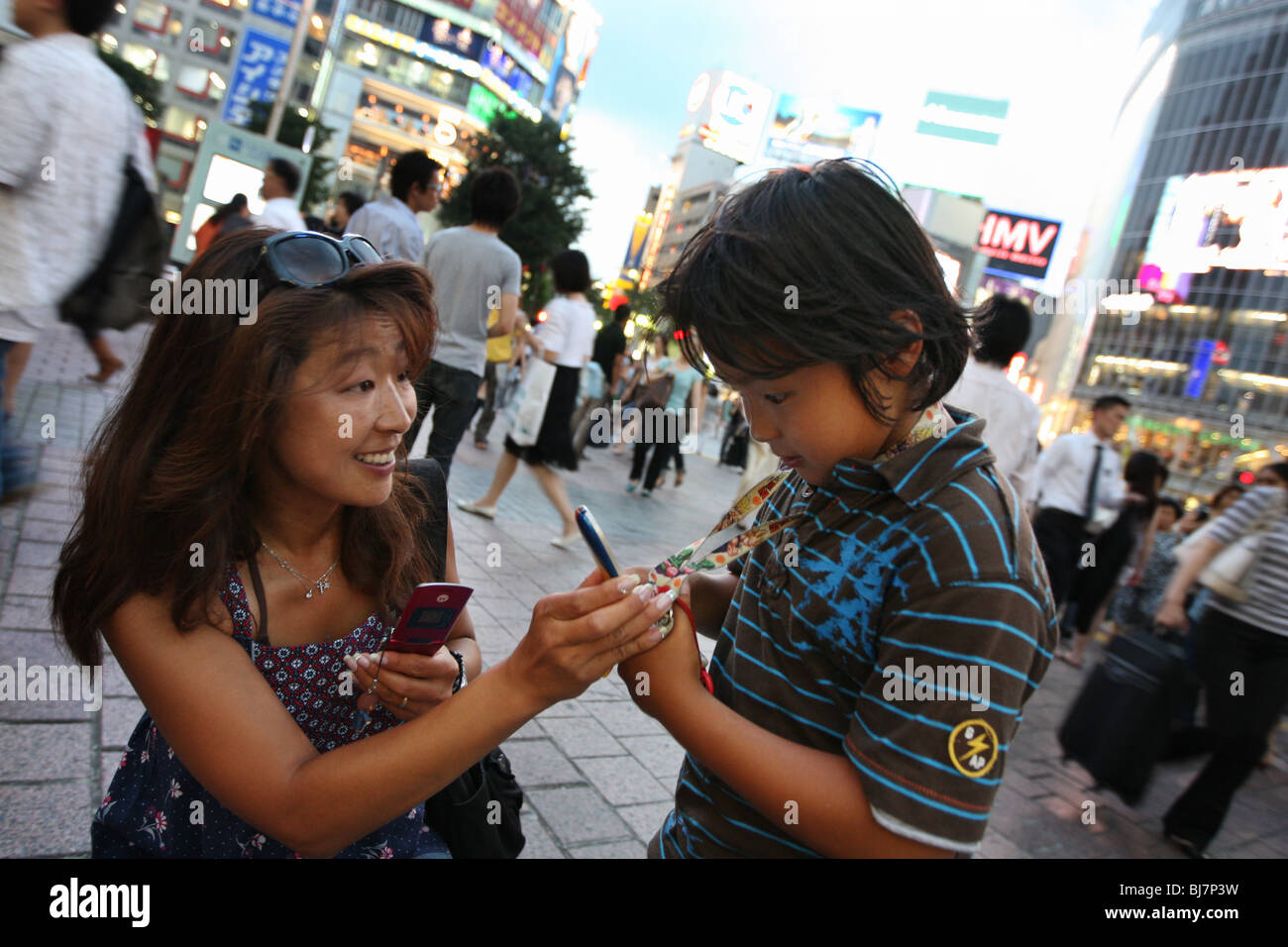 Japanese mother and son with their mobile telephones, Tokyo, Japan. - Stock Image