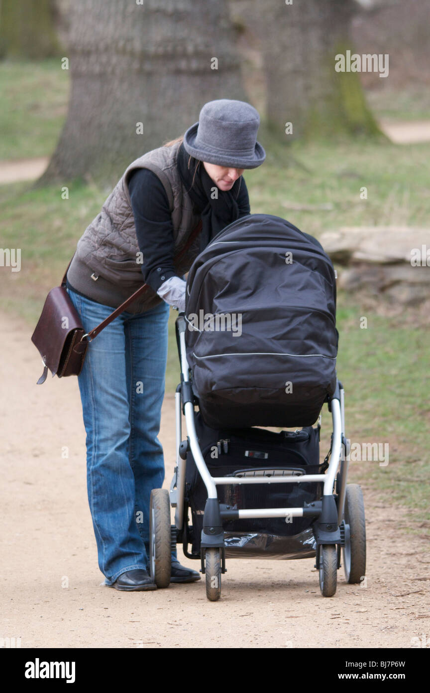 Young Mother tending to her baby in a pushchair while walking in Richmond Park, Surrey, England Stock Photo