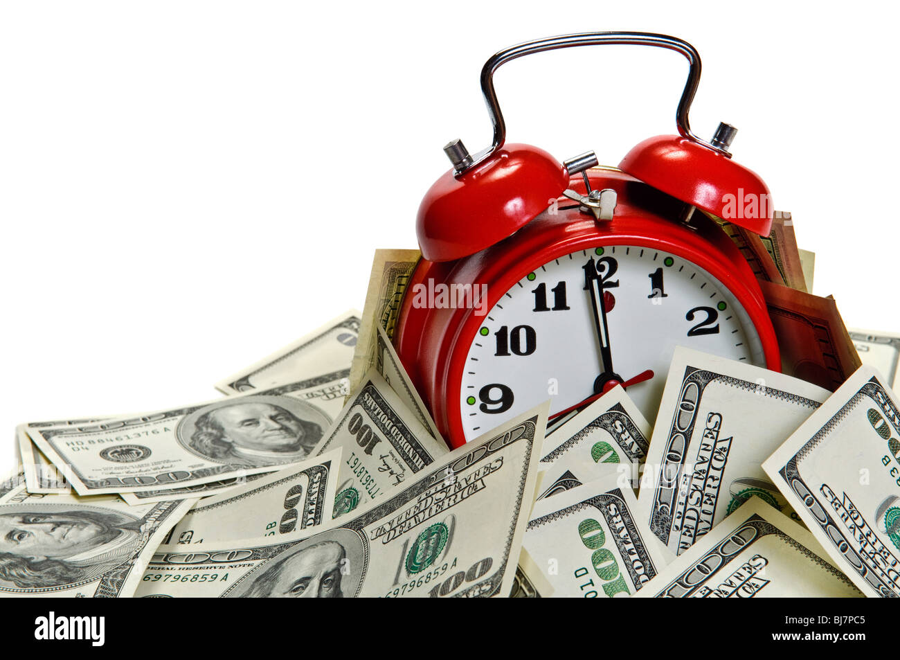Retro styled alarm clock covered pile of money isolated on white. Time is money concept - Stock Image