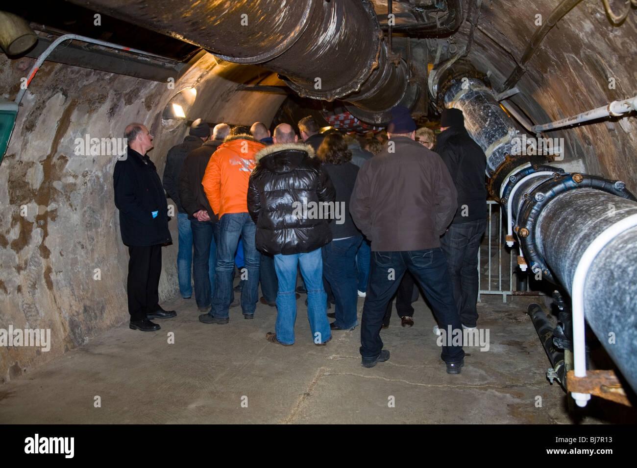 Group of tourists / tourist party tour inside Paris sewers – Visite Des Egouts De Paris / sewer museum visit in - Stock Image