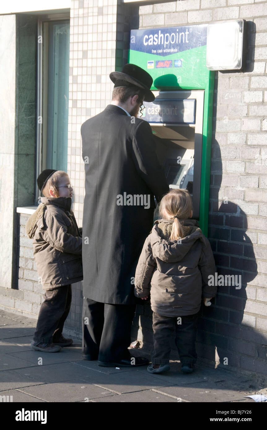ORTHODOX JEW AND CHILDREN AT CASHPOINT MACHINE IN STAMFORD HILL  LONDON - Stock Image