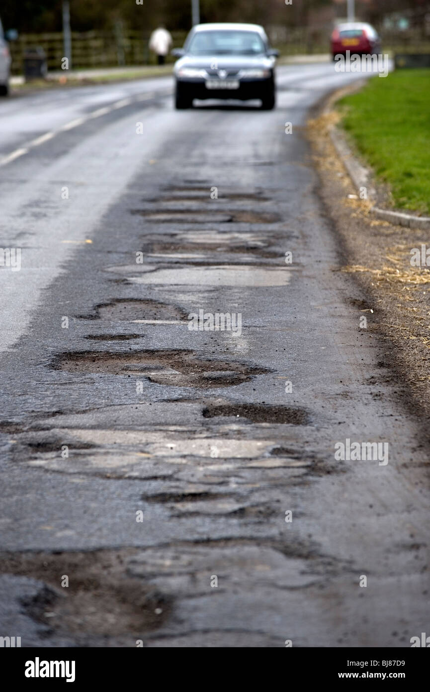 A car approaches potholes in Priory Road, Hull, East Yorkshire, UK. - Stock Image