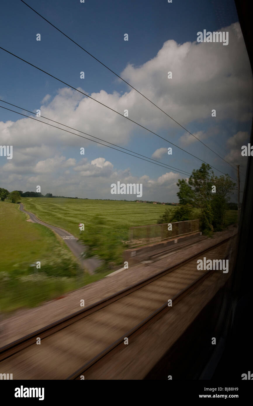 View of countryside from train, country road, green fields, blue sky, rail road Stock Photo